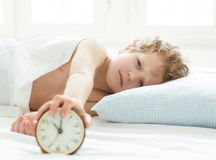 Angry little boy lying on the bed and stopping alarm clock in morning. Stock Images