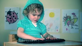 Angry little boy pounding computer keyboard with sulky face stock video footage