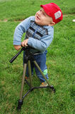 Angry little child playing with tripod Stock Image
