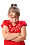 Angry little girl with arms crossed isolated Stock Image