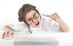 Angry little girl and computer stock photo