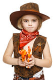 Angry little girl cowboy holding guns. Angry little girl wearing cowboy costume holding guns pointing at camera, over white background Royalty Free Stock Photo