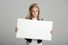 Angry little girl holding a blank sign Royalty Free Stock Photos
