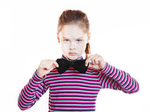 Angry little girl wearing striped blouse and black bow-tie Royalty Free Stock Photography