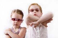Angry little girls. Sisters in sunglasses on white Royalty Free Stock Photos