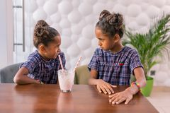 Cute little daughters looking at each other angrily after arguing in cafeteria stock photo