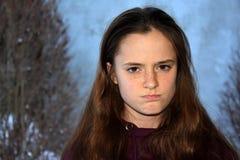 Angry looking teenage girl seeks revenge. Angry looking teenage girl with wonderful brown hair looks very angry and seeks revenge stock photo
