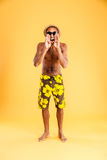 Angry mad african man in swimwear standing and shouting. On a orange background Royalty Free Stock Photography