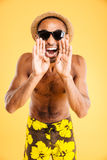 Angry mad african man in swimwear standing and shouting. Angry mad african man in swimwear and sunglasses standing and shouting  on a orange background Stock Image