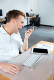 Angry mad businessman talking on mobile phone and shouting. Angry mad young businessman talking on mobile phone and shouting in office Royalty Free Stock Image