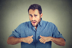 Angry, mad, unhappy guy pointing at himself as if to say, you mean me? Royalty Free Stock Photos