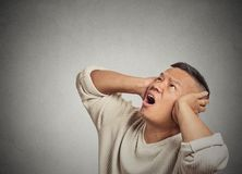 Angry mad unhappy stressed man covering his ears looking up Royalty Free Stock Photo