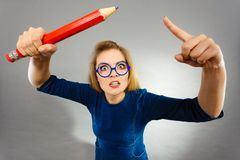 Angry woman holds big pencil in hand Royalty Free Stock Photography