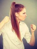 Angry mad woman clenching fist punching on gray. Stock Photos