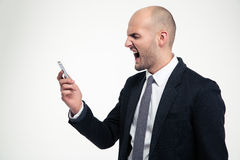 Angry mad young businessman holding mobile phone and screaming. Over white background Stock Photography