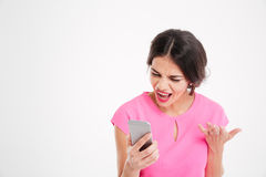 Angry mad young woman shouting and using mobile phone Royalty Free Stock Photography