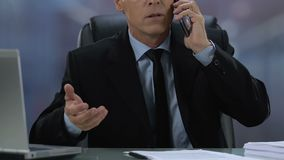 Angry male boss talking on phone sitting in office, workload pressure, anxiety. Stock footage stock video footage