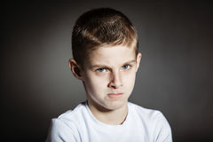 Angry male child posing pensively in dark room. Angry male child with brown hair and blue eyes wearing white shirt posing pensively in dark room Royalty Free Stock Photos