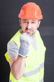 Angry male constructor showing fist and looking irritated. Angry male constructor in protection equipment showing fist and looking irritated against black Royalty Free Stock Images