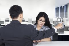 Angry male manager expels his employee. Picture of angry male manager expelling his employee while pointing out and sitting in the office Royalty Free Stock Photos