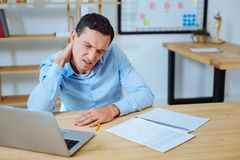 Angry male person making faces. Have pain. Tired office worker closing eyes and opening mouth while touching his neck Royalty Free Stock Photos