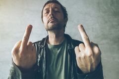 Angry male punk showing middle finger. As form of aggressive impolite dissatisfaction gesturing. Retro toned, selective focus Royalty Free Stock Photos