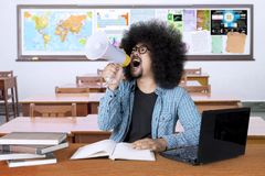Angry male student learning in the classroom. Picture of a male college student looks angry and screams on a megaphone while learning in the classroom Royalty Free Stock Photography