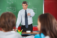 Angry Male Teacher Pointing At Students. In classroom Royalty Free Stock Image