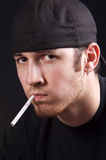 Angry Man. Young man in black hat with cigarette looking angrily toward camera Royalty Free Stock Photos