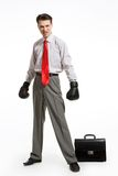Angry man. Portrait of aggressive businessman wearing boxing gloves over white background Royalty Free Stock Photography