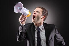 Angry man announcing via loudspeaker. Angry businessman announcing via loudspeaker royalty free stock photography