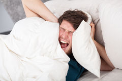 Angry man awoken by a noise. Angry man in bed awoken by a noise Stock Photos