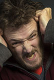 Angry Man. An angry man with a bad temper tearing his hair out Stock Photo