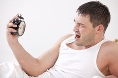 Angry man in bed with alarm clock Stock Image