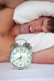 Angry man in bed annoyed by his alarm clock Stock Images