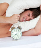 Angry man on bed stressed by his alarm clock Royalty Free Stock Photos