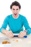 Angry man in blue sweater making cigarettes with device for ciga Royalty Free Stock Photos