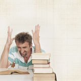 Angry man and books. Angry man with learning difficulties Stock Photography