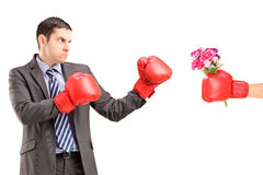 Angry man with boxing gloves hitting a hand with boxing glove an Royalty Free Stock Image