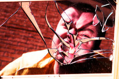 Angry man in broken glass. Man's angry face distorted by broken glass stock photo