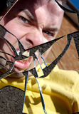 Angry Man in Broken Mirror. The face of an angry man reflected in a broken mirror stock photos