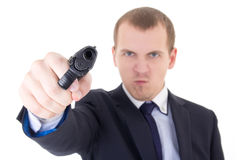 Angry man in business suit shooting with gun isolated on white Stock Image
