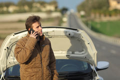 Angry man calling roadside assistance for his breakdown car. In a road in winter Stock Images