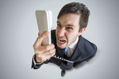 Angry man is calling and shouting to the telephone. View from above Royalty Free Stock Photos