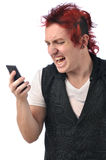 Angry man on cell phone. Young angry man with wild red hair yells into cell phone Royalty Free Stock Images
