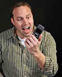 Angry man with cellphone. Angry man shouting at cellphone, black background Stock Image