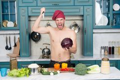 Angry man chef with sexy torso stab knife at cabbage Royalty Free Stock Photography