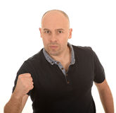 Angry man with clenched fist. Angry middle aged bald man with clenched fist, white background Stock Photos