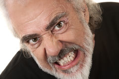 Angry Man Clenches Teeth. Angry Caucasian senior citizen over isolated background clenching teeth royalty free stock photos