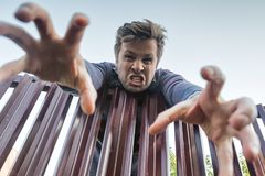 Angry man climbs furiously over the fence, breaking the boundaries of private property and pulling his hand down. Trying to grab something Stock Images